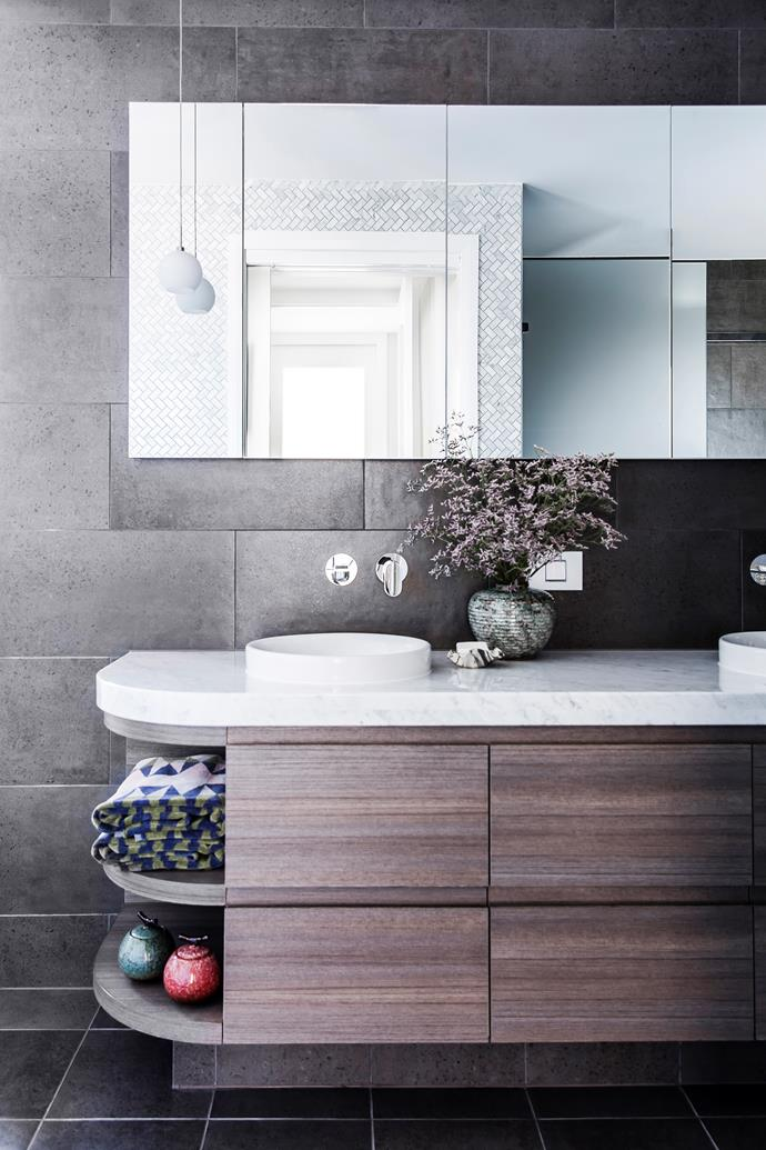 While the choice of tiles was locked into the contract, Matthew was able to personalise the bathrooms with custom-made joinery, including this sleek vanity unit. Vanity in 'Matrix' laminate in Dark Teak Eleganza, from Cleaf. Quantum Quartz benchtop in Carrara Bianco.