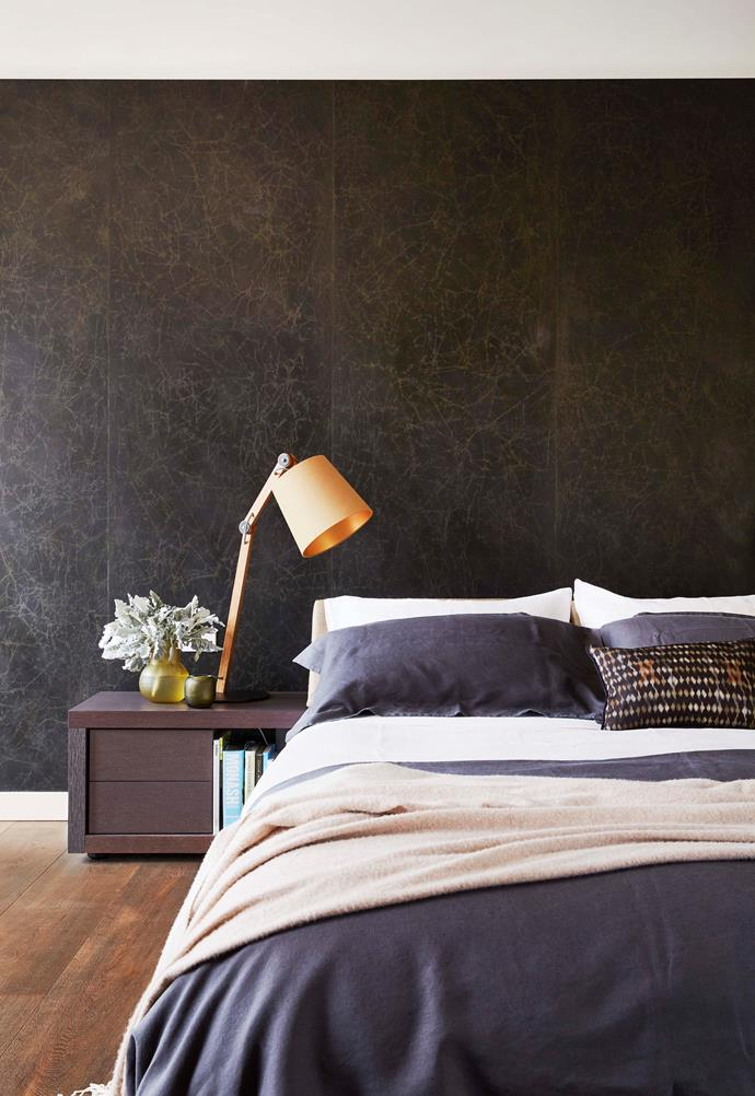 Handmade wallpaper sets up a moody backdrop in the main bedroom.