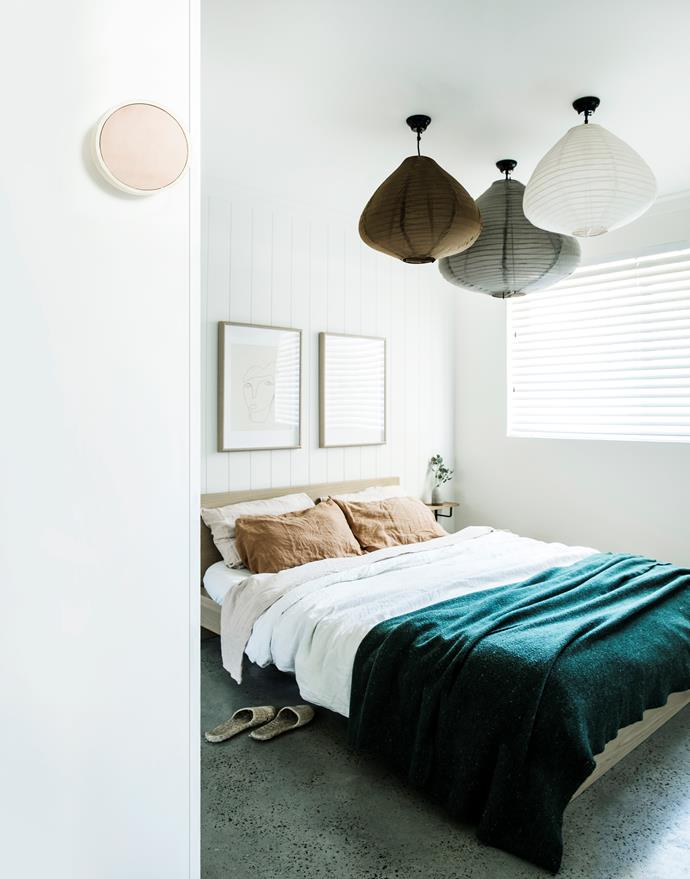 The earthy tones and curved shapes of the HK Living pendant lights add to the bedroom's tranquil vibe.