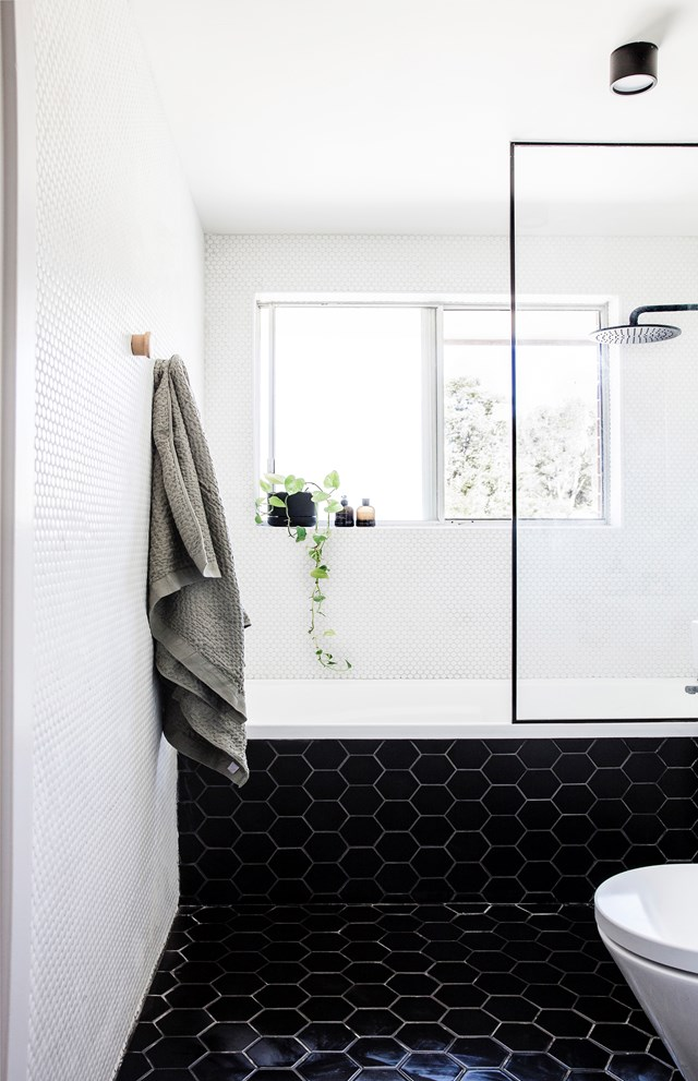 Hexagonal matte black floor tiles create a classic, yet modern look in this monochrome bathroom.