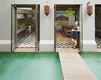 Homeowner standing in the doorway of home overlooking an internal courtyard pool