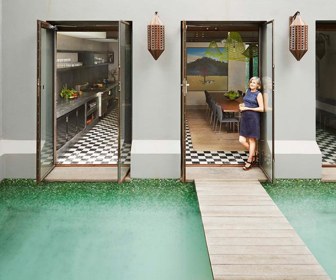 Homeowner standing in the doorway of home overlooking an internal courtyard pool
