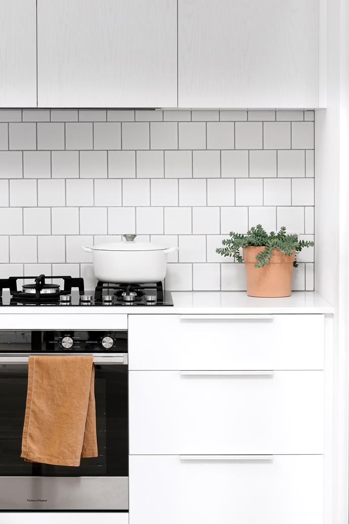 A Caesarstone benchtop in Pure White and white 'Brick Bond' tiles in Matt, keep this kitchen feeling light and airy.