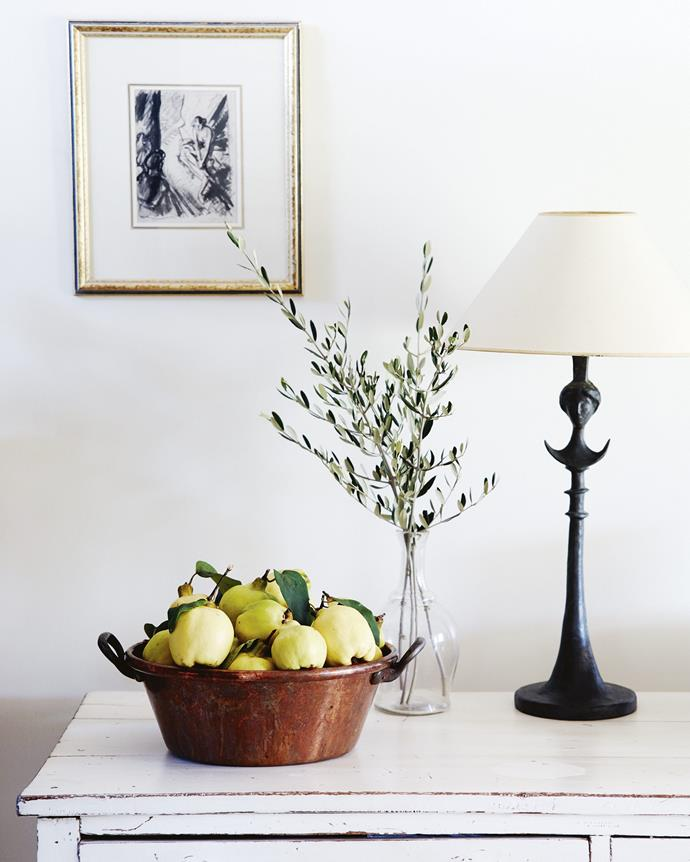 *Carnival Radio Times* by English artist Steven Spurrier hangs above a copper pan filled with freshly picked quinces. *  Photography: Mark Roper   Styling: Tess Newman-Morris*