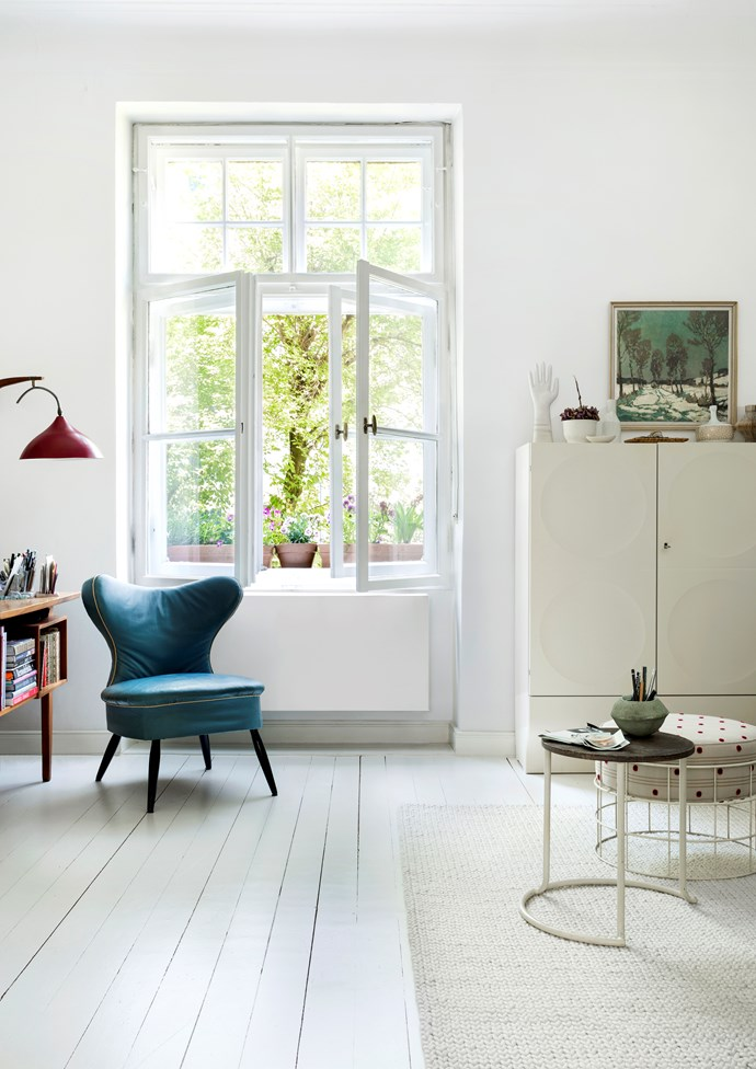 """An open window looking out to a blossoming tree invites greenery into Christine's mostly white living room. The textural knitted wool rug provides a layer of warmth, while the round side table is a rare early [Aino Aalto design](https://www.homestolove.com.au/alvar-aalto-17794