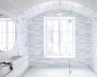 Blue and white bathroom with subway tiles and curved ceiling