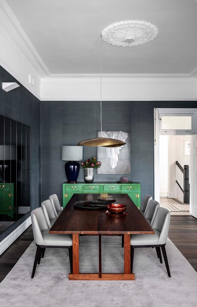 A green sideboard adds a pop of colour to the subdued formal dining room. A brass pendant light hovers above the dining table.