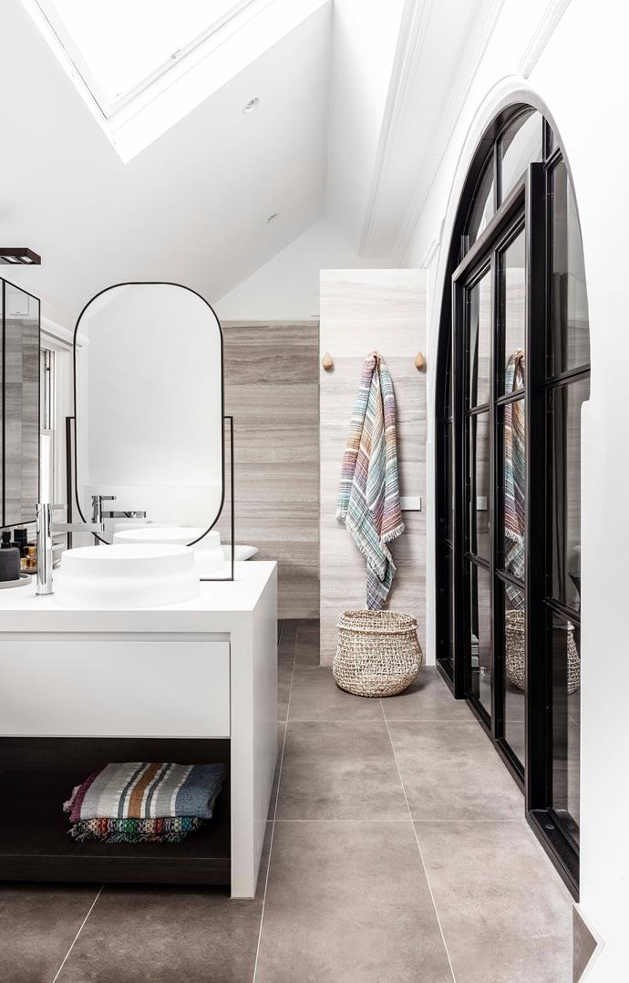 The curve of the steel-arch doors is echoed by a round-edge mirror in the luxurious ensuite bathroom.