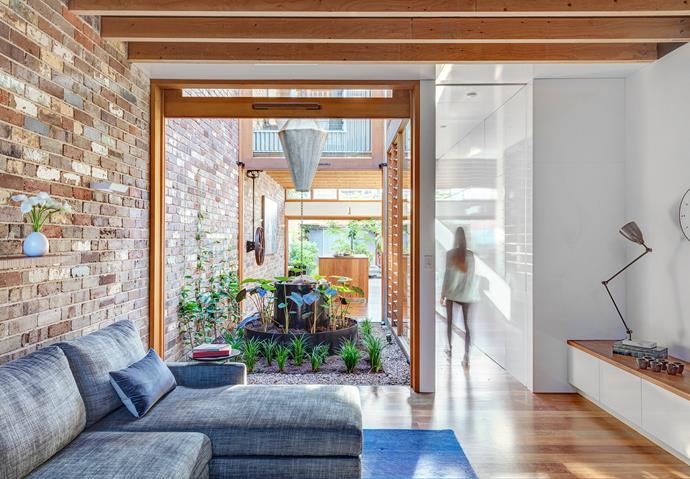Recycled dry-pressed bricks in a home designed by CplusC Architectural Workshop. The brick feature wall creates continuity between the indoor and outdoor living spaces.