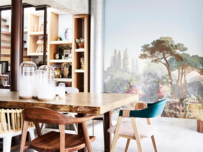 "The family's dining table is a custom creation featuring marble on one side and timber on the other. It can be reconfigured into three different tables. Scenic wallpaper by Zuber and the Brokis ""Muffin"" lamp add a touch of drama to the space."