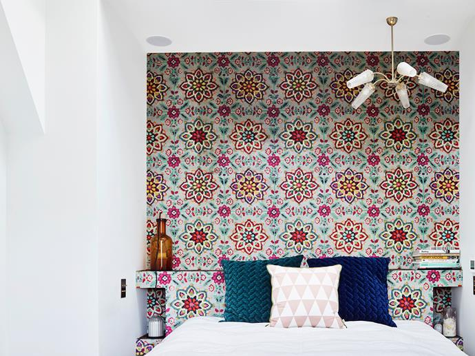 In the master bedroom, a custom bedhead acts as inbuilt shelving where Laura and Pascal can store and display their belongings. Laura opted to cover it and the wall behind in geometric wallpaper from Designers Guild, and also created cushion covers using fabric from the same brand.