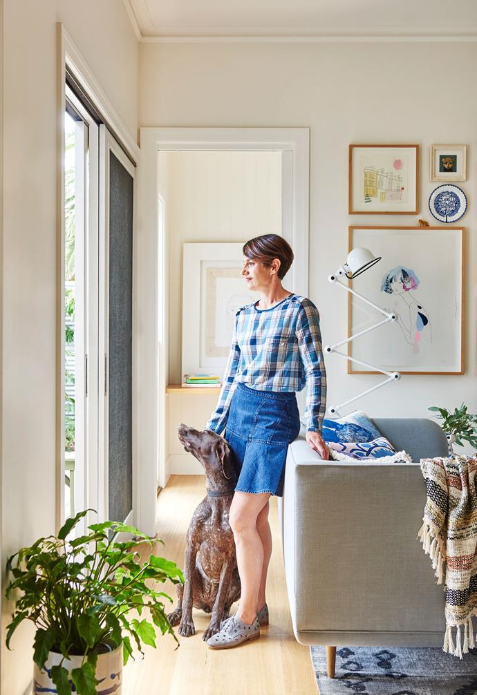 """**Living area**  Homeowner Kristen with family dog Mosel. Artworks: (in background room) by Kristen Paul, (on wall, clockwise from top left) *Whiteladies Road* by unknown artist; Artwork by unknown artist; Plate by [Rob Ryan](https://robryanstudio.com/ target=""""_blank"""" rel=""""nofollow""""); Artwork by Kat Macleod, [Lamington Drive](http://lamingtondrive.com/ target=""""_blank"""" rel=""""nofollow""""). Angus & Celeste ceramic planter (in foreground), [Goose](https://www.goosestore.com.au/ target=""""_blank"""" rel=""""nofollow"""")."""