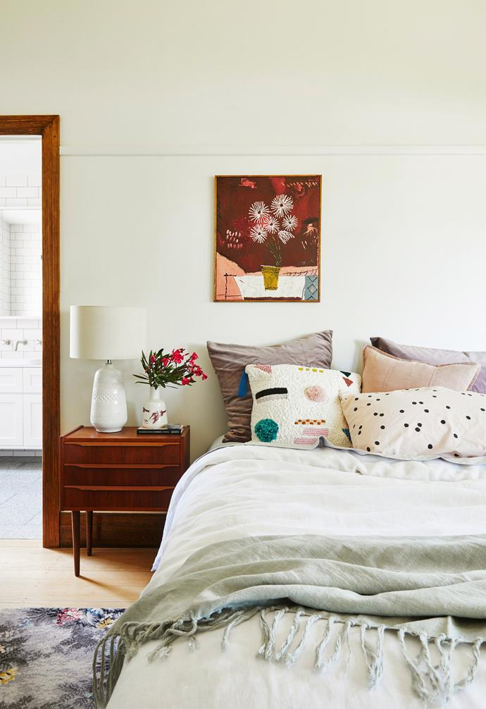 """**Master bedroom** All eyes are drawn to the still-life above the bed, Reverse Sunsets by Jordan Kerwick. Soft colour comes courtesy of Kip&Co bedlinen and an Eadie Lifestyle blush panelled cushion and grey tasselled throw, all from Goose. The floor rug is a repurposed carpet square from the home of Kristen's great-aunt. Embroidered Anthropologie cushion, La Cerise Sur Le Gateau pillowcase & 'Alibi' table lamp, [Goose](https://www.goosestore.com.au/ target=""""_blank"""" rel=""""nofollow""""). Side table, [Great Dane](https://greatdanefurniture.com/ target=""""_blank"""" rel=""""nofollow""""). Wall painted in Interior Expressions Low-sheen acrylic paint in 'Organic 1', [Haymes Paint](http://www.haymespaint.com.au/ target=""""_blank"""" rel=""""nofollow"""")."""