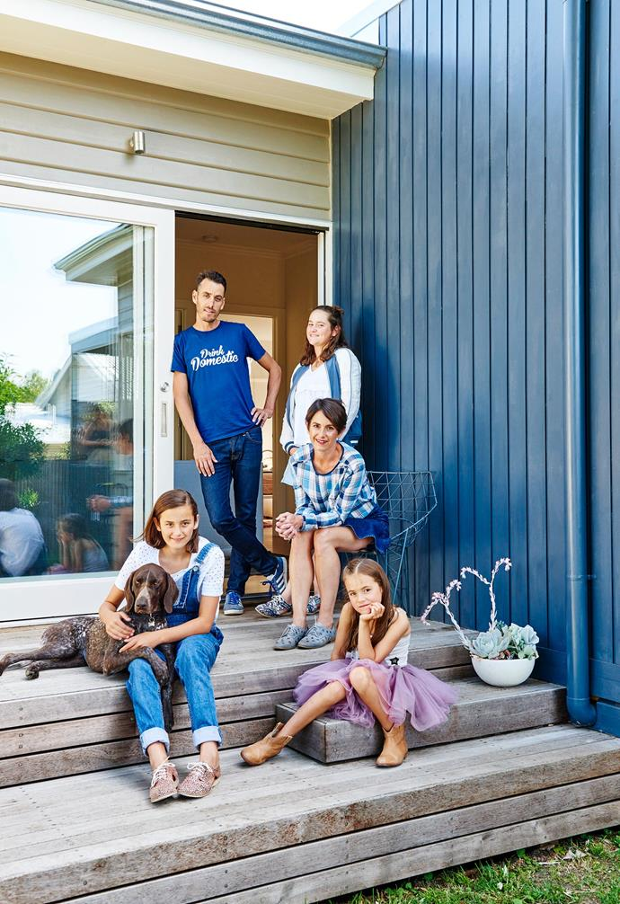 """**Exterior** Kristen relaxes with Steven, Isabel, Claudia, Sofia and Mosel. The new merbau timber deck will continue to weather naturally over time. """"We love having meals out here,"""" says Kristen. """"One of my best friends lives around the corner and jokes that when the outdoor lights are on, it means the bar is open, so she pops around!"""" Exterior wall painted in Weathershield Low-sheen in 'Charcoal Essence', [Dulux](https://www.dulux.com.au/ target=""""_blank"""" rel=""""nofollow"""")."""