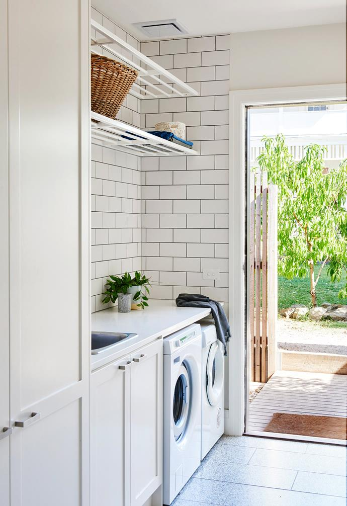 """**Laundry** """"Having a separate laundry is wonderful,"""" says Kristen, who finds the floating shelves above the bench particularly useful for storage."""