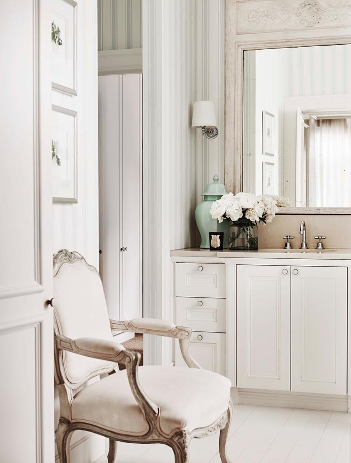 The master ensuite bathroom was one of the first stages of the renovation. It now features a classic style with striped blue wallpaper and a reupholstered Louis V armchair.