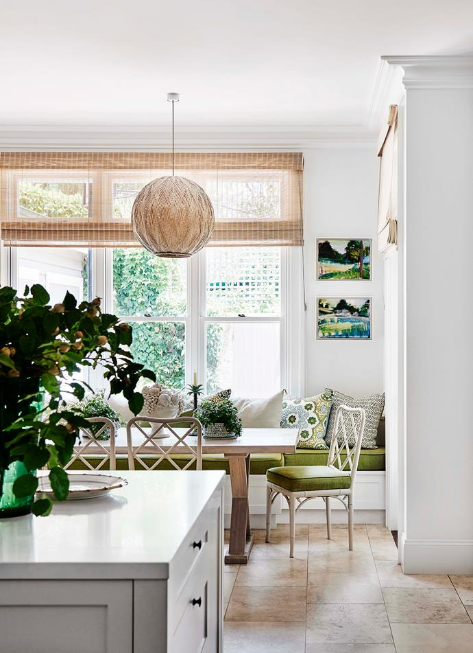 In the family dining room, woven bamboo blinds and a statement pendant light are offset by rich green upholstered seating.