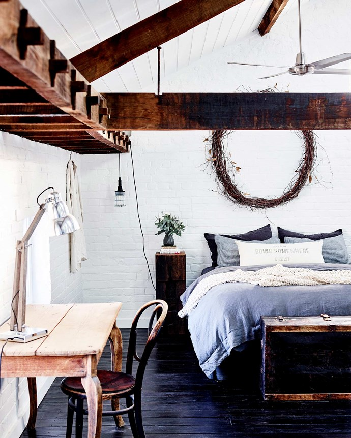 """Exposed ironbark mortice-and-tenon beams feature in the main bedroom. The hanging light is from [Tomolly](https://www.instagram.com/tomolly_carcoar/ target=""""_blank"""" rel=""""nofollow"""")."""