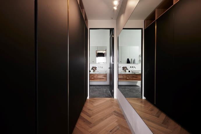 **Walk-in wardrobe -** Tucked behind their master bedroom is a chic walk-in wardrobe featuring matt black cabinetry with brass detailing.
