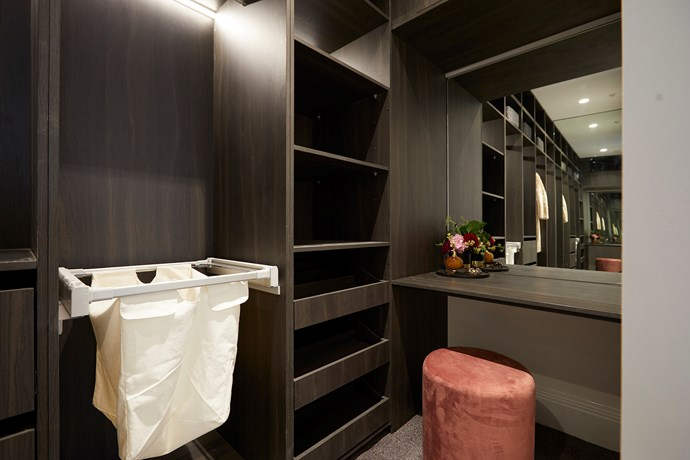 The dark-hued walk-in wardrobe feels luxurious and is fit for a master bedroom suite.
