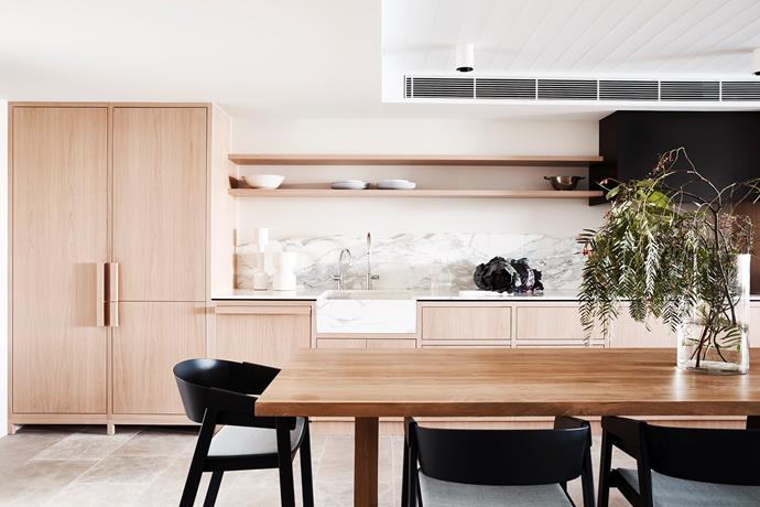 """**'Making waves' by Emma Say & Jade Nottage of [Tom Mark Henry](http://www.tommarkhenry.studio/ target=""""_blank"""" rel=""""nofollow""""):** The owner of this beachside Sydney apartment works overseas for much of the year and wanted a luxurious yet low-maintenance home he could look forward to spending time in, a place where he could feel relaxed as soon as he set foot in the door. While a large kitchen wasn't essential, an inline layout featuring a wall of whitewashed-oak cabinetry maximises efficiency in the space. V-groove lining boards on the ceiling (at right and also in the living areas) reference traditional weatherboards, while the undulating grain in the limestone floor and rough-edged marble splashback evoke the movement of waves and drifting sand. *Photo:* Damian Bennett"""