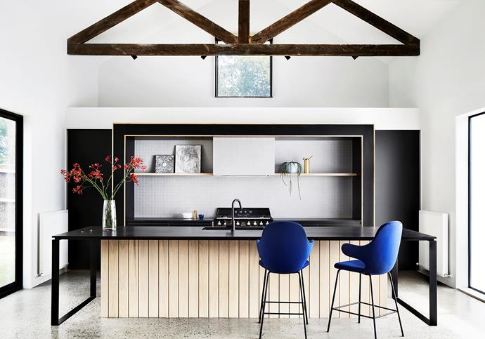 """**'Fine form' by [Sisällä Interior Design](https://sisalla.com.au/ target=""""_blank"""" rel=""""nofollow""""):** """"The kitchen was designed to 'float' in the space,"""" says interior designer Lauren Li of this beautifully detailed design in a Mornington Peninsula home. Pleasing symmetry and thoughtful materiality underpin this room, part of a development by Mode Projects. The work zone is framed by black laminate joinery, which projects from a blade wall. A generous butler's pantry is tucked behind. Subtly textured pale mosaic tiles in the recess are expertly paired with the black composite-stone benchtops and powdercoated steel-framed island bench. Timber planks add another layer of interest and reference the region's holiday-home heritage. *Photo:* Tess Kelly"""