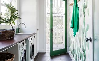 Laundry with green wallpaper and green glass door.