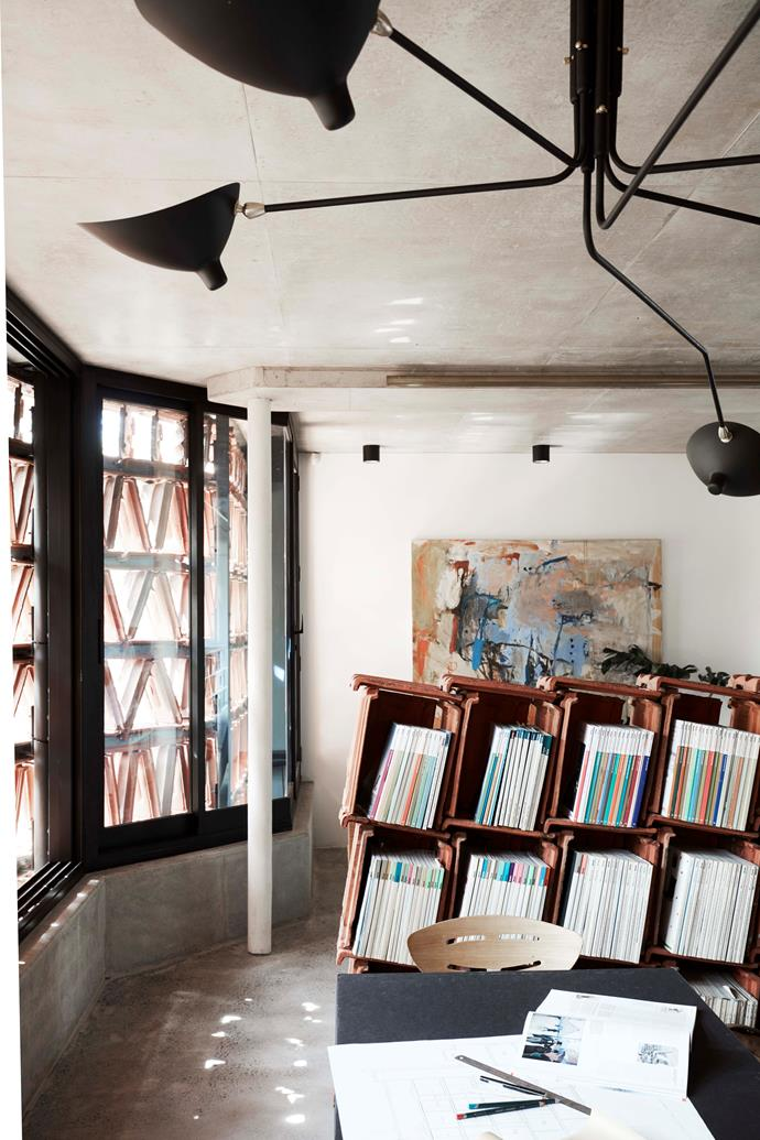 Terracotta tiles are used internally as a bookshelf; custom brass lighting by Oliver Tanner; artwork by Ann Thomson.