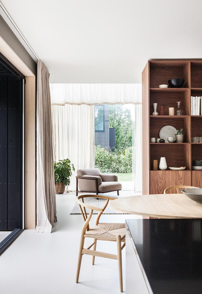 "**Living area** A Bolia armchair looks out on the garden. ""We like using different materials, which gives the abstract architecture a warm feeling from the inside,"" says Holly."