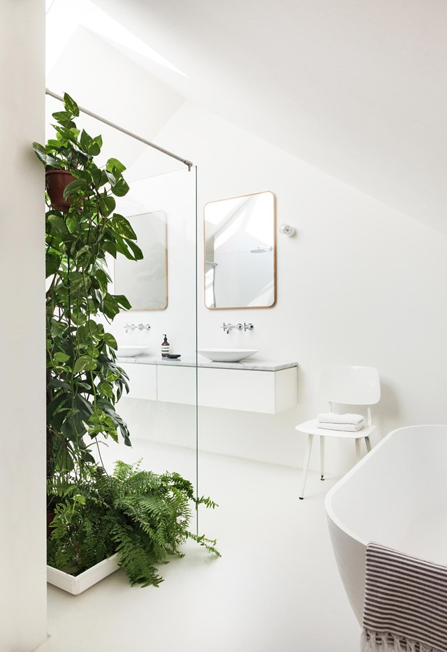 "Rays of sunshine streaming in through a pair of skylights are magnified by an all-white palette in this bathroom. The only colour comes from a [cascading indoor plant] and a cluster of lush ferns. This [eco-friendly pre-fab home](https://www.homestolove.com.au/prefab-eco-friendly-home-19148|target=""_blank"") was built within an experimental sustainable neighbourhood in the Netherlands."