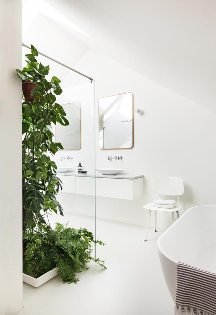 "**Ensuite** A simple white palette works brilliantly with Corian basins, Zazzeri tapware and a Carrara marble benchtop. The finishing touches are an Ahrend 'Revolt' chair and a mirror from Dutch website home24.nl. A zen garden has been established in the ensuite. ""The large plant is a Monstera deliciosa Swiss cheese plant,"" says Stefan. ""It's great for humid spaces, as its roots take up moisture from the air. This has already grown 50cm!"""