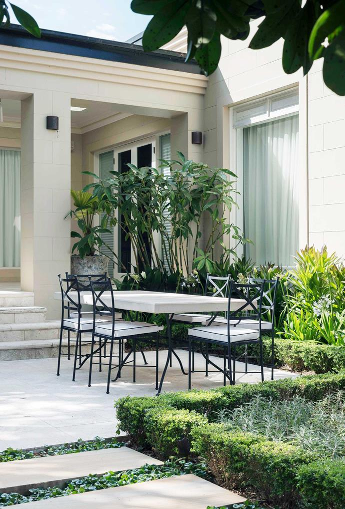 The paved outdoor dining zone is surrounded by soothing layers of green.