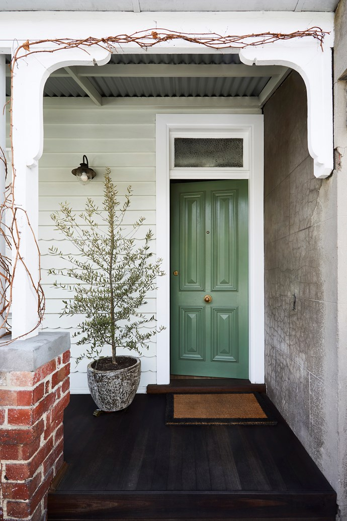 An olive tree grows in the concrete pot, while Virginia creeper twines over the verandah. Weatherboards in Dulux Lamb's Ears Half.
