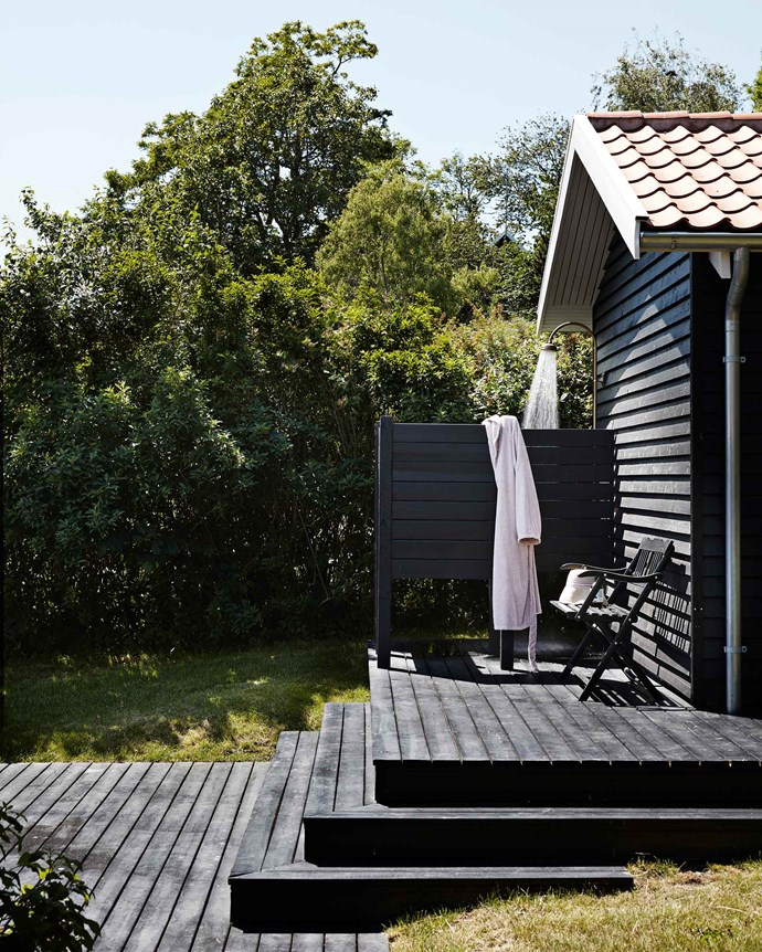 The family's outdoor shower is located at the end of the gabled annexe and comes in handy after a day at the beach. The house is full of people every summer during school holidays, as well as on weekends throughout the rest of the year. The family are keen sailors and love spending time on the water waterskiing and surfing — there's always water-related gear packed into the car and boat as they set off on holidays.