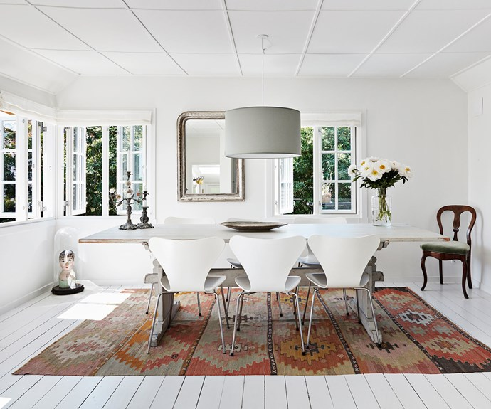 """Arne Jacobsen Series 7 chairs in white surround the dining table Jette sourced from her own store, along with the kilim rug and mirror. The interiors are a wonderful blend of old and new, with treasured family heirlooms adding character to the mix. """"I'm usually a fan of more muted colours, but when it comes to a summer house, it's OK to crank up the colours and have a bit of fun with it,"""" says Jette."""