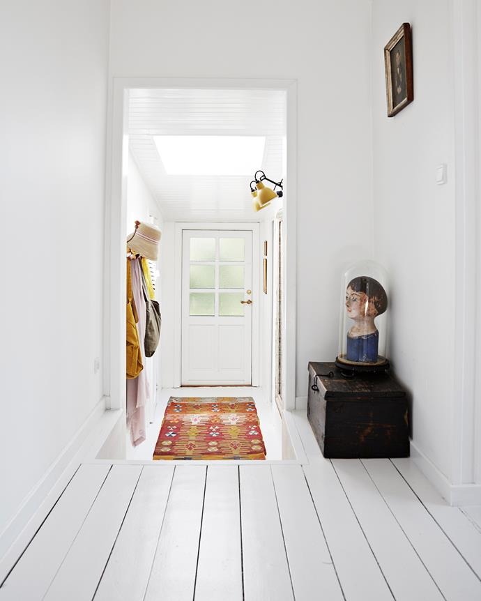 A rug and vintage wares from Jette's store decorate the hallway leading to the front door.  The white walls and floorboards make the perfect backdrop for the subtle splashes of colour Jette has added in the form of soft furnishings, framed artwork, rugs and accessories.