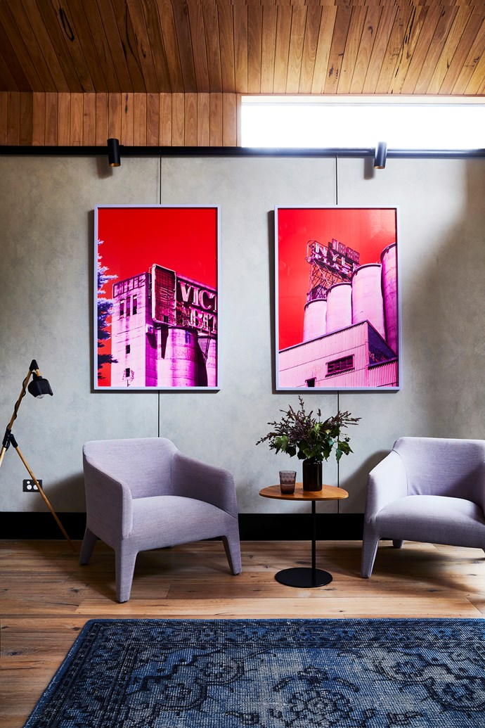 These artworks by Kate Ballis are a colourful feature on the cool grey fibre-cement wall. The steel railings can be read as a witty reference to traditional picture rails. 'Kelly' armchairs, from Jardan.
