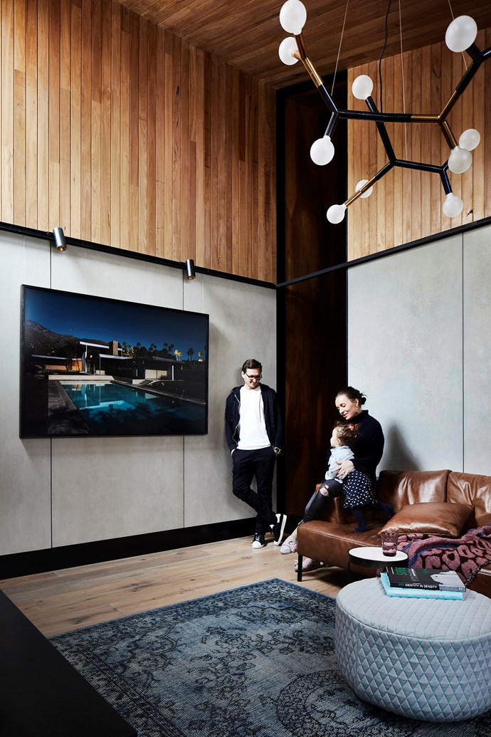 Michael and family love this contemporary corner, where a photograph by Tom Blachford presides. The walls are clad in silvertop ash and CSR fibre-cement panels. Sofa, Ross Didier. Ottoman/coffee table, Anaca Studio.