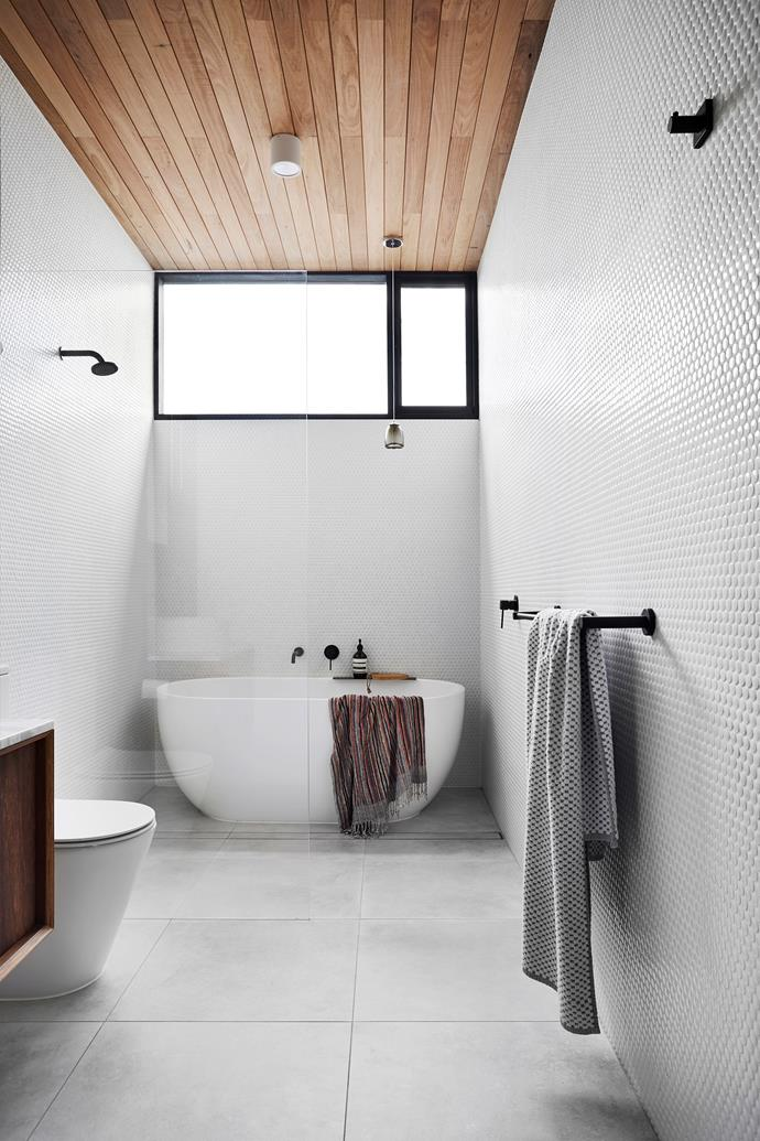 Penny-round mosaics from Tiento Tiles and a Kado 'Lux Petite' bath from Reece amp up the luxury in the main bathroom.