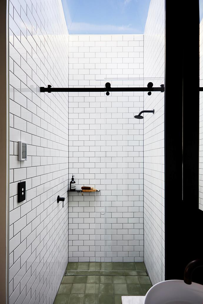 A skylight over the shower lets the light flood in to this subway-clad ensuite.