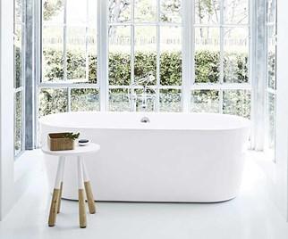 Freestanding bathtub in front of a bay window