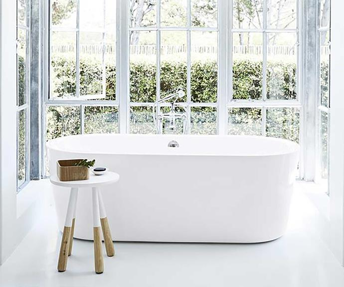 Freestanding bathtub in front of a bay window