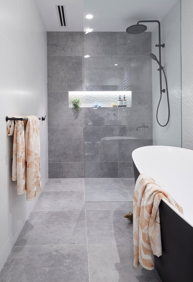 The concrete tiles and black fixtures make the space feel modern, while the freestanding tub and Zuster vanity with terrazzo handles add a sense of luxury and elegance.