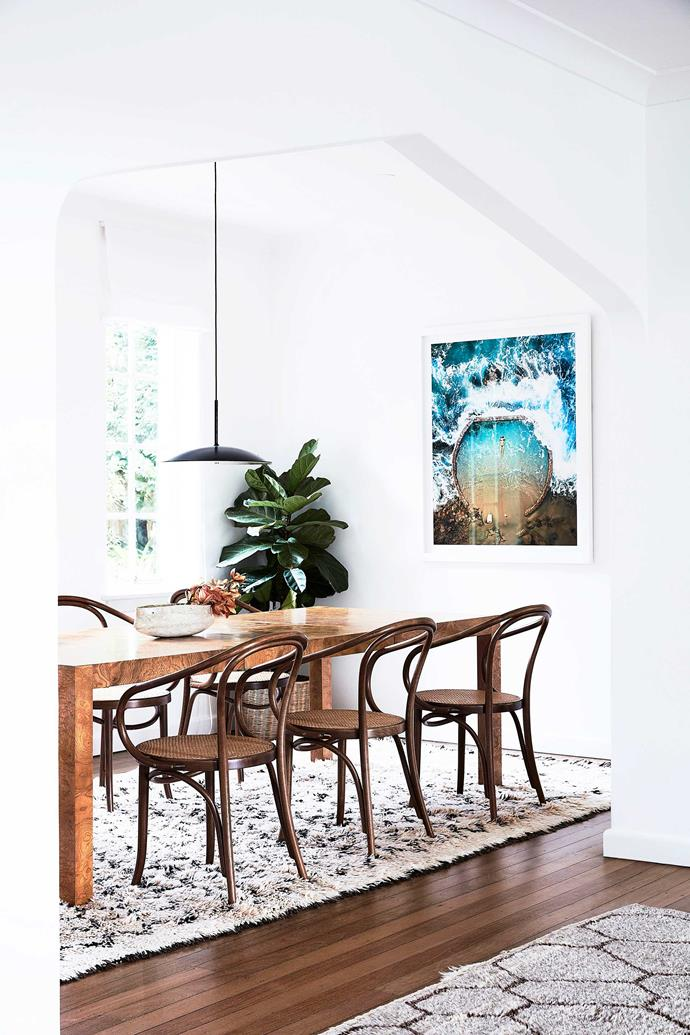 In the dining room, Le Corbusier walnut cane seats by Thonet surround a Milo Baughman burl olive wood dining table. The pendant light is from Radar. The rug is a vintage Beni Ourainv.