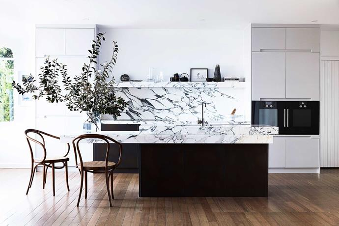"""The Arabescato marble in the kitchen was chosen for its warmth. This depth is complemented by the island's Treasury Bronze cabinets and doors painted in Murobond """"Raw Earth"""". The tapware is from the Brodware """"Yokato"""" range and there's plenty of space to pull up a Thonet cane seat and eat in."""