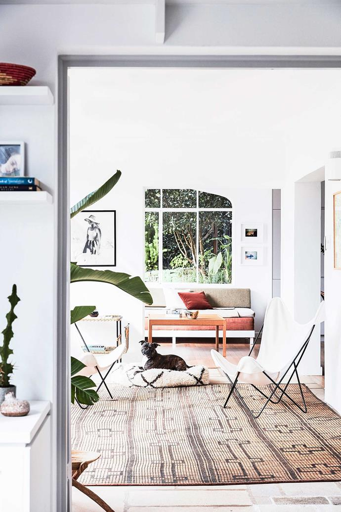 A vintage Tuareg mat from Jason Mowen adds texture to the living room. White butterfly chairs have been paired with banquette seating designed by Kate Manning. A Sikker Hansen print and two framed works by Gia Coppola hang on the walls, but the true star is the lush garden view.