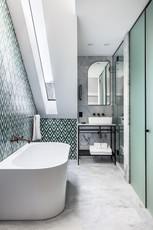 "Eye-catching emerald green tiles in rhomboid scales are balanced out with a frosted glass door in a similar tone, more subtle marble tiles and antique brass tapware in this [boutique hotel bathroom](https://www.homestolove.com.au/bathroom-trends-inspired-by-boutique-hotels-19168|target=""_blank"")."