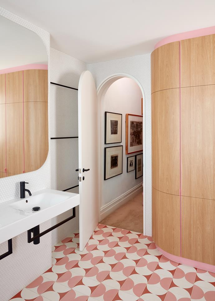 Take an original feature or single design element and carry it throughout your bathroom look. Here, an arched doorway  is echoed in the curves of the tiles, mirror and timber cupboard. *Photo: Sean Fennessy*
