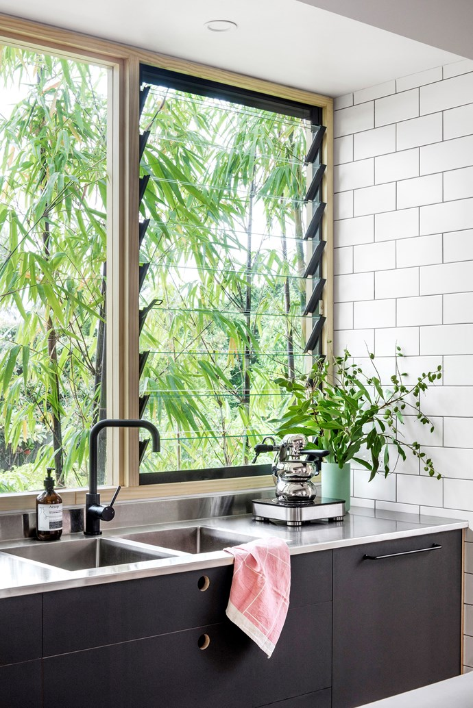 The stainless-steel benchtop extends up the wall to form a seamless shallow splashback, so there is no tight angle that's hard to clean.