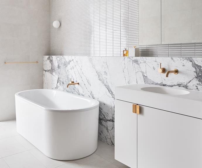White bathroom with marble wall and brass tapware